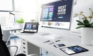 a desk with a laptop and monitor on it